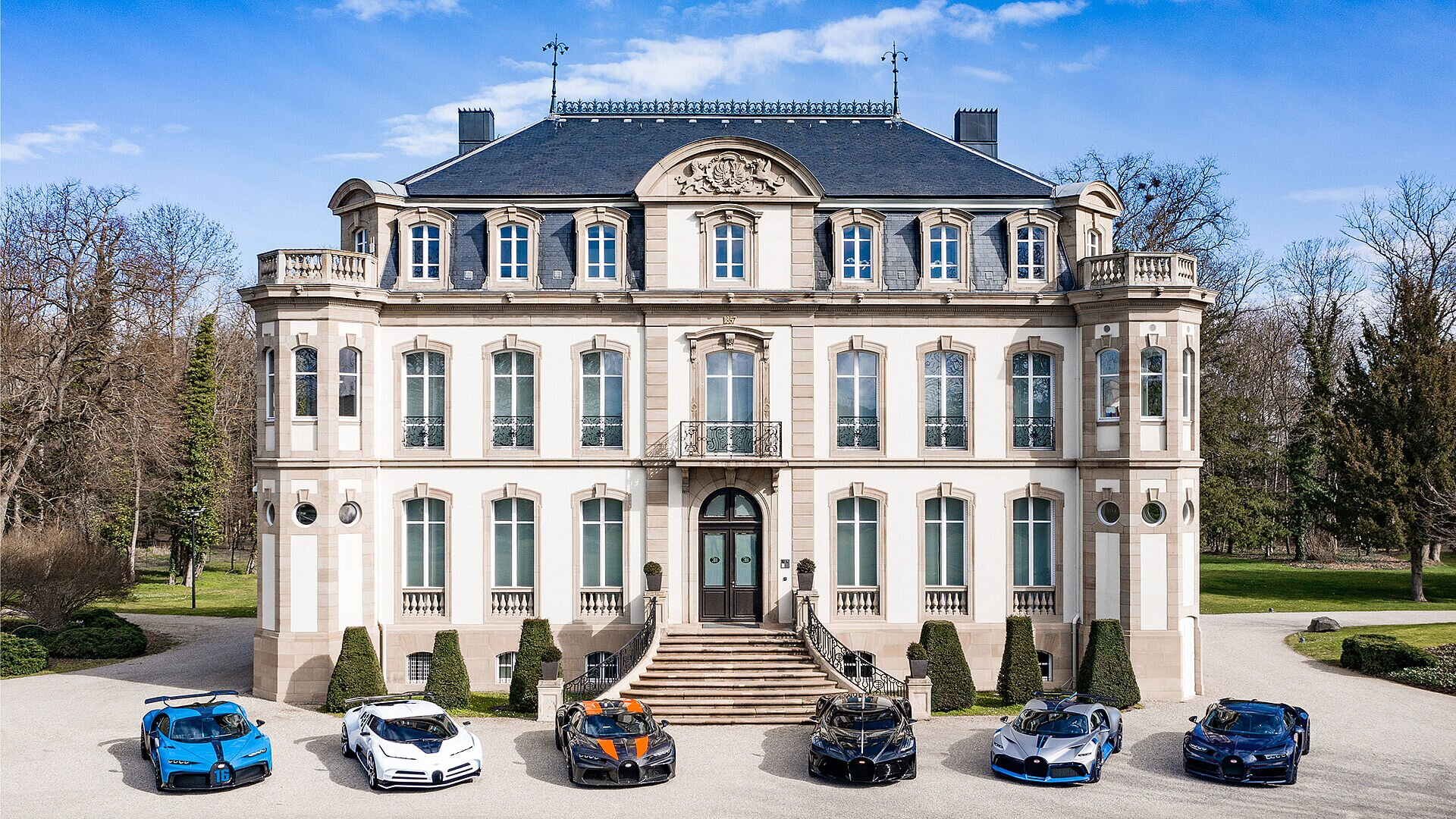 [Translate to Français:] Chiron Pur Sport, Centodieci, Chiron Super Sport 300+, La Voiture Noire, Divo und Chiron Sport stand in front of Château St. Jean in Molsheim (left to right)